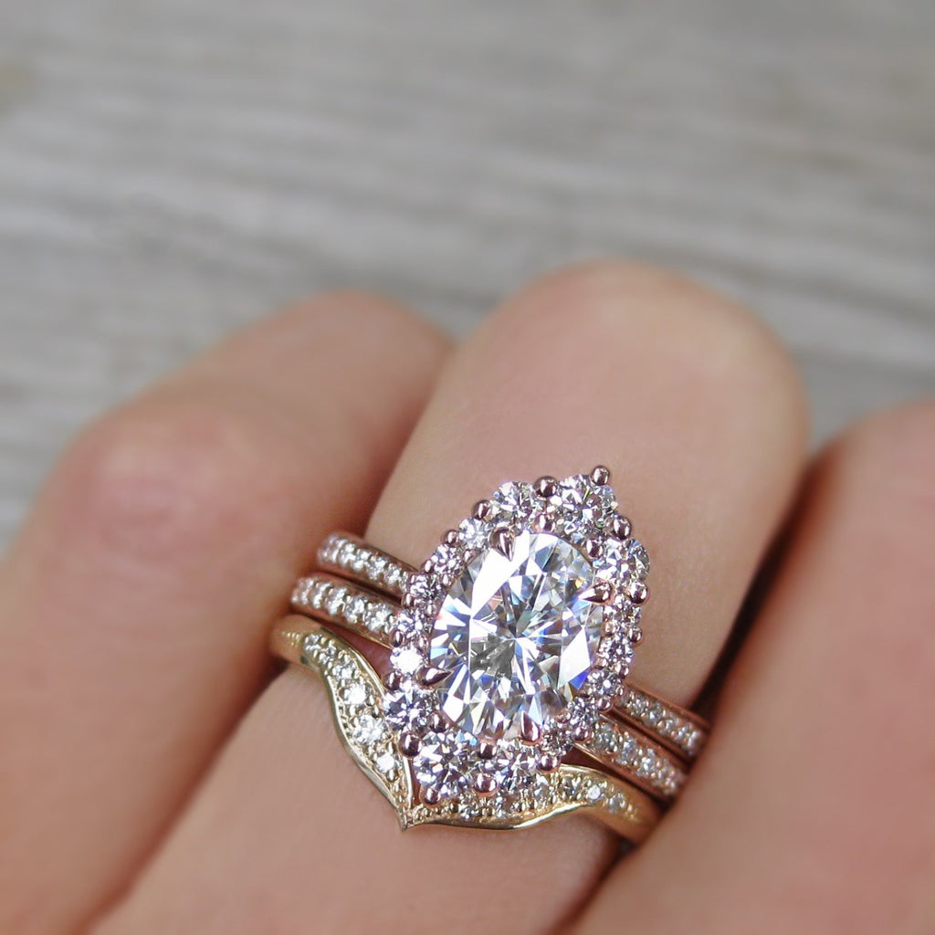 Vintage-inspired and low-profile 1.5ct lab-grown oval diamond halo engagement ring stacked with two pave diamond wedding bands