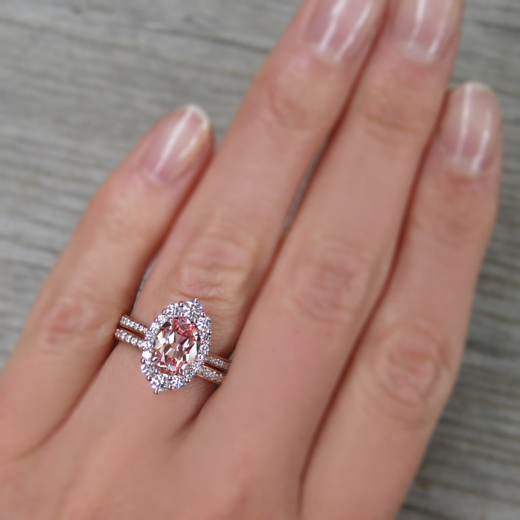Oval Peach sapphire engagement ring with a conflict-free diamonds halo stacked with a diamond wedding band