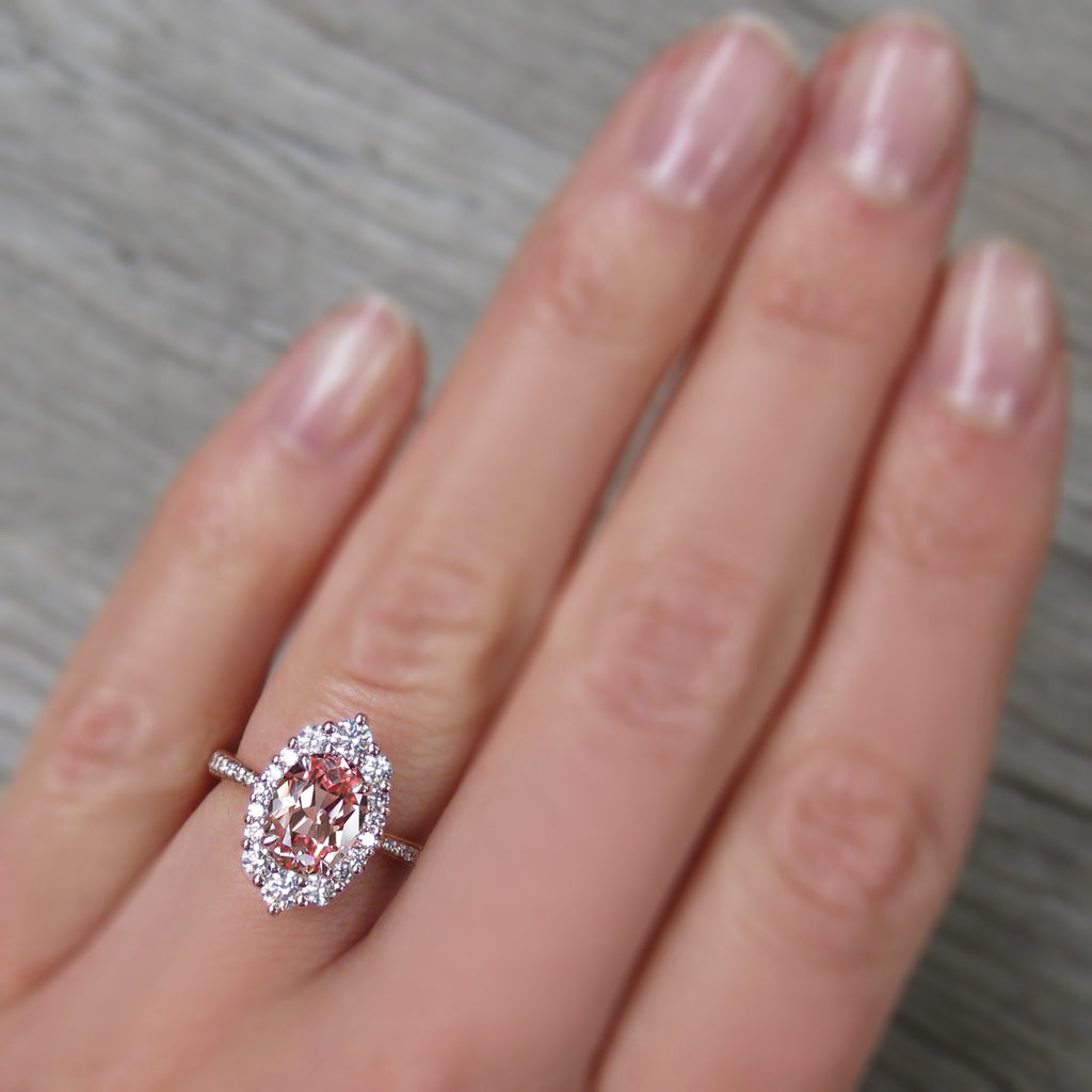 Low-profile Oval Peach sapphire engagement ring with a conflict-free diamonds halo