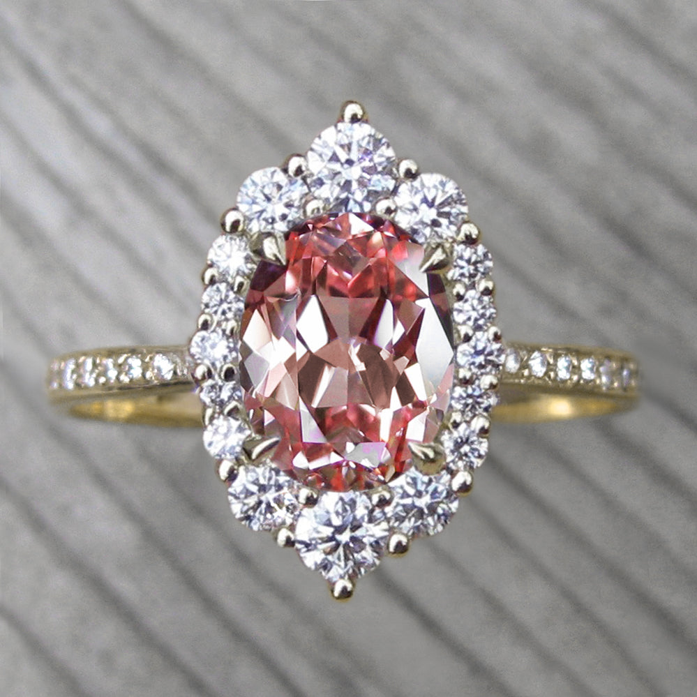 Oval Peach sapphire engagement ring with a conflict-free diamonds halo