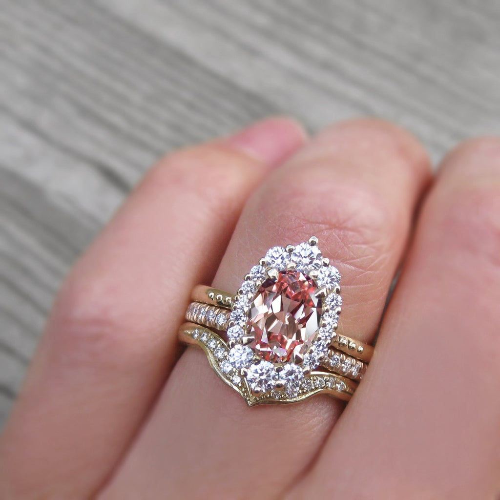 Low-Profile Oval Peach-Pink Sapphire and Diamond Halo Engagement Ring stacked with Diamond Wedding Bands