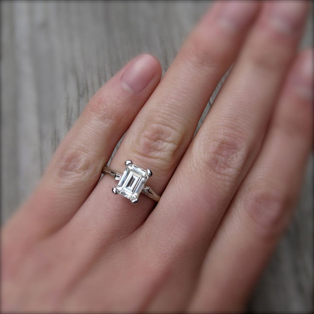 Eco Friendly feather ring with a Forever One emerald cut moissanite in yellow gold