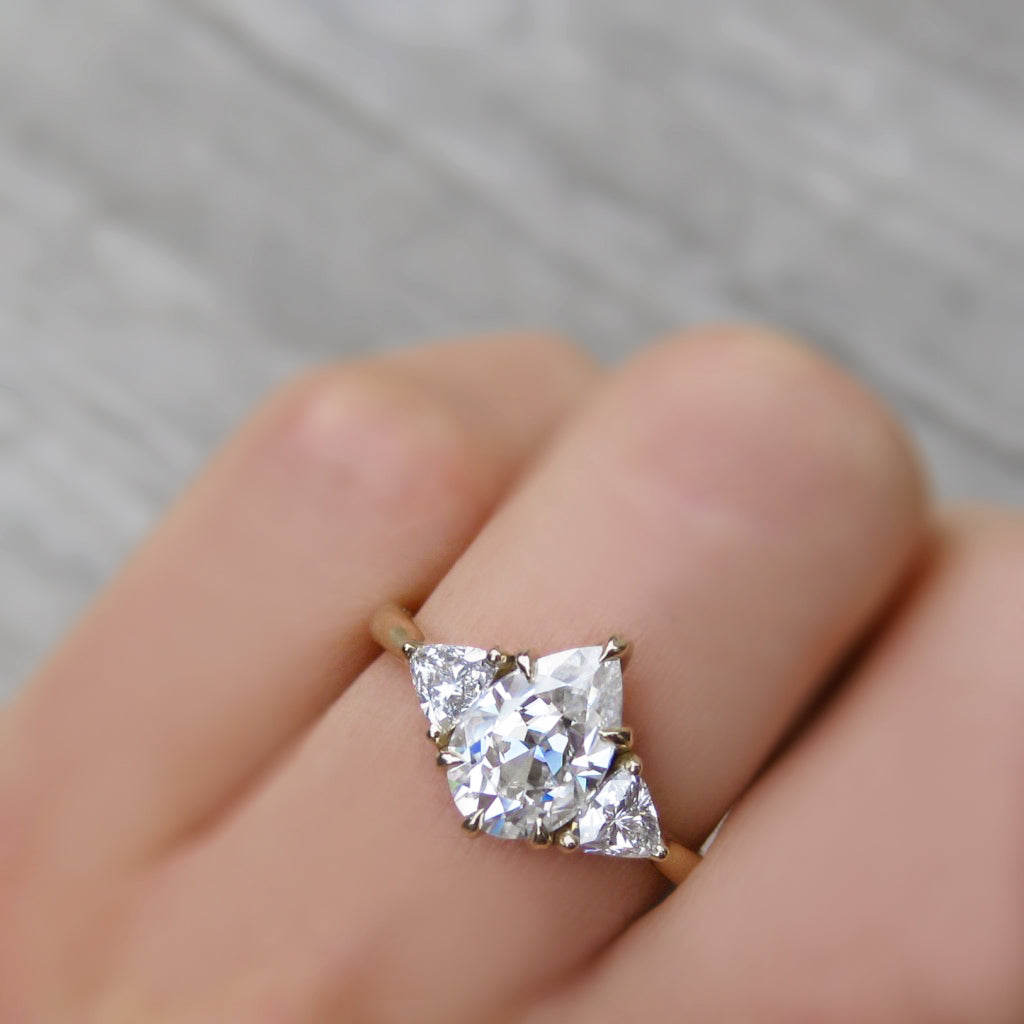 Charles and Colvard Forever One pear moissanite three stone engagement ring