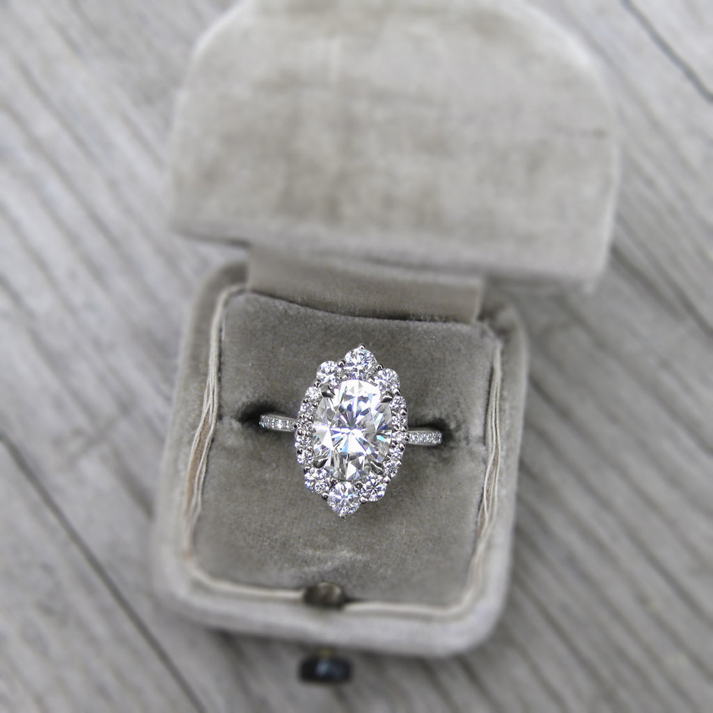 Oval moissanite halo engagement ring with diamonds in 14k gold modeled in engagement ring box