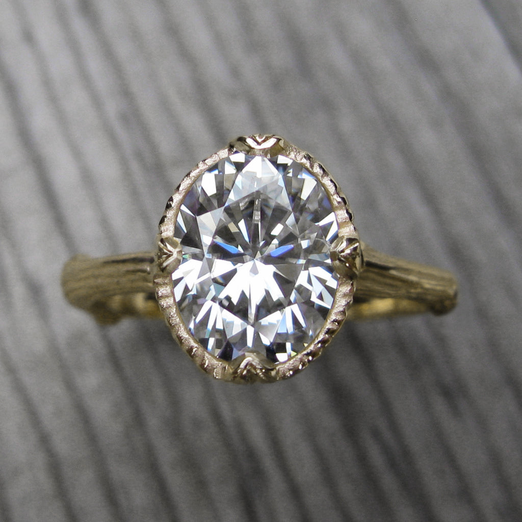 2ct yellow gold twig solitaire engagement ring with a Forever One oval cut moissanite