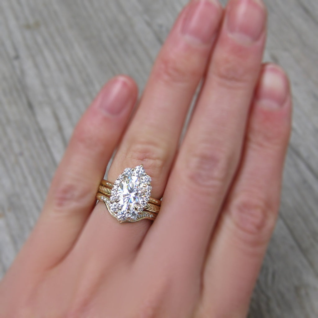 Oval moissanite halo ring in yellow gold with Chevron and Feather Wedding Bands