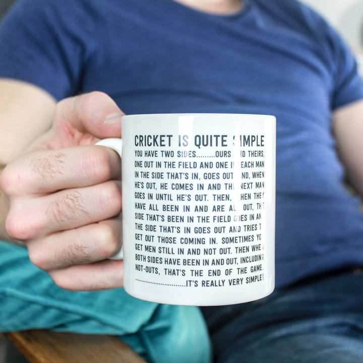 Male hand holding a black and white mug with the funny cricket quote 'Cricket is Quite Simple' printed on it. The man is wearing a blue tshirt and jeans and resting his forearm on a turquoise cushion.