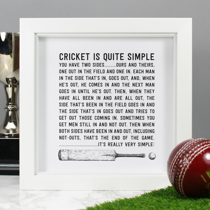 The 'Cricket is Quite Simple' Quote framed art print product photo shows the art print displayed in a white 8by8 box frame. The quote is black and white and incudes an ink illustration of a vintage cricket bat and cricket ball at the bottom of the art print. The framed print is displayed against a grey background with a trophy, and a red cricket ball and section of green astroturf in the foreground of the photograph.