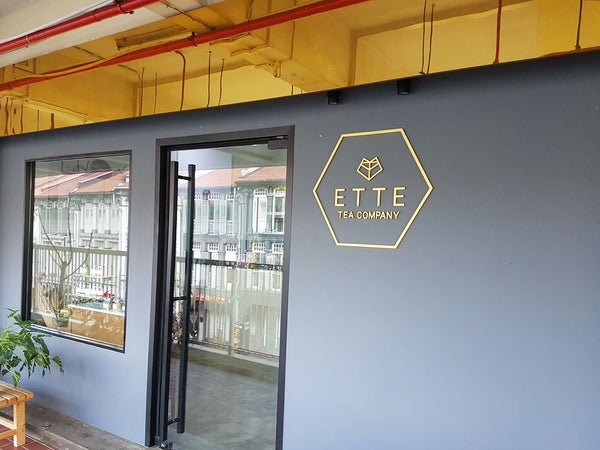 ETTE TEA store front in Chinatown Singapore. With gold sign board, grey walls and a it's hexagon logo.