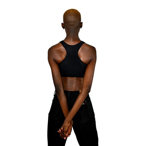 Model shows off a black racerback binder, back to the viewer with hands clasped behind the back.