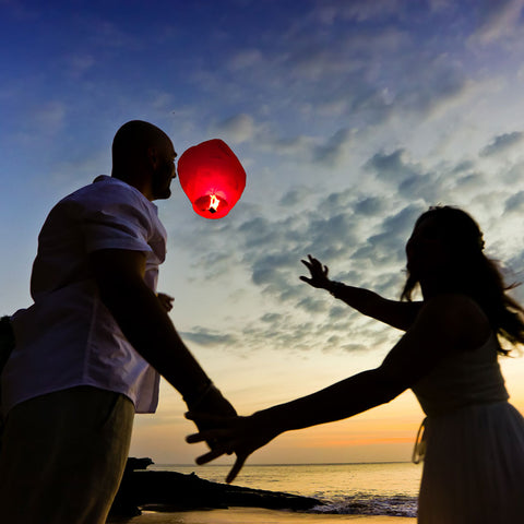 A Canadian couple lunching a rice paper flying lantern in the sky