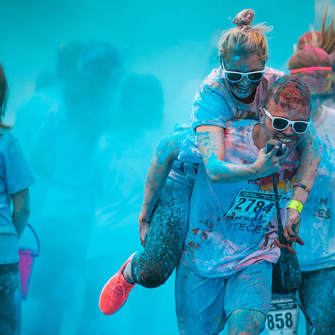 A couple running together through blue Colour Powder