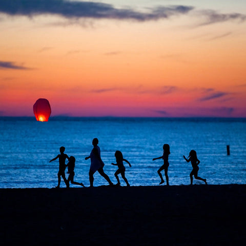 Canadian Family at the beach ad looking at a flying lantern going away in the sky