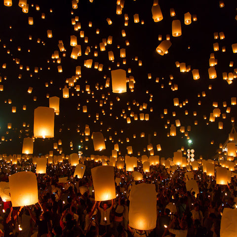 Alot of people at a festival using chinese flying lantern