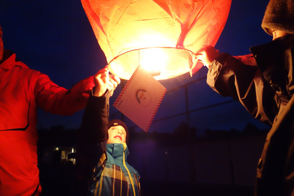 people launching a christmas lantern
