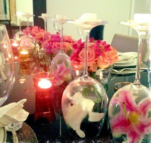 upside down wine goblets with candle and flowers