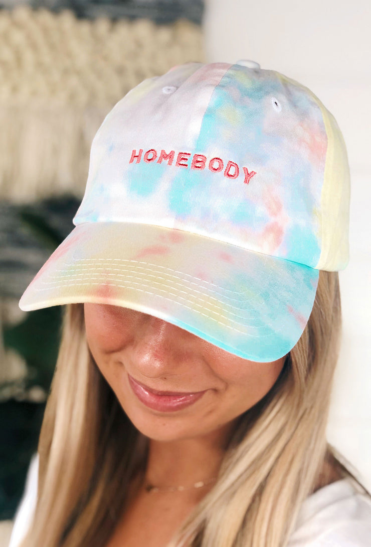 "Friday + Saturday: Tie Dye Homebody Hat, multicolor tie dye adjustable hat with ""homebody"" embroidered in coral stitching on the front"