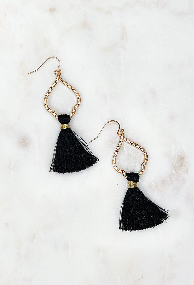 Isabella Fringe Earrings in Black, gold spade shaped earrings with black tassel hanging off on a hook backing