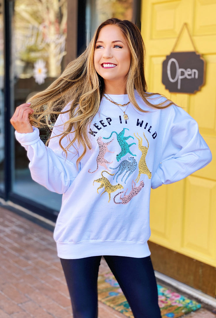 Keep it Wild Cheetah Sweatshirt, white sweatshirt with multicolored cheetahs on the front with the slogan 'keep it wild'