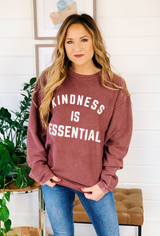 NOON:30 Kindness is Essential Corded Sweatshirt, dark burgundy corded sweatshirt with 'kindness is essential' graphic on the front in white lettering