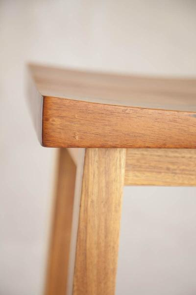 This is a close up of left corner edge of a bar chair. These high bar chairs are made from blackwood. The height can be customised to fit into most spaces.