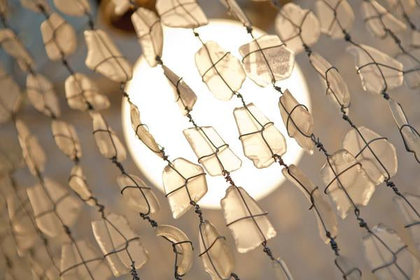 This is a chandelier made with 500 glass beads lit up to create an ambience in the bedroom. The hoops of our chandeliers are made from galvanised steel from old wine barrels.