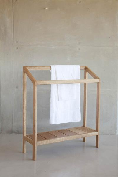 This is a double towel rail with a shelf, and a white towel draped over it.