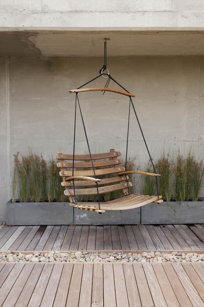 A wine barrel, patio swing chair, made from reclaimed oak, suspended by black yachting rope.