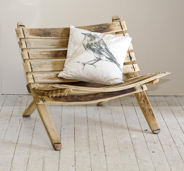 This is a loveseat made from oak, with a cushion on it.