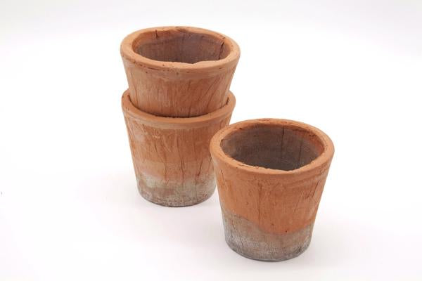 These are small terracotta pots stacked in two, on on top of the other. These garden plant pots compliment any outdoor setting.