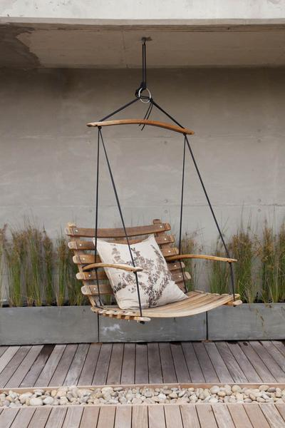 This is a wooden swing chair made from wine barrel staves, hanging over a patio. This hanging chair is accessorised with an eco cushion and is suspended by black yachting rope.