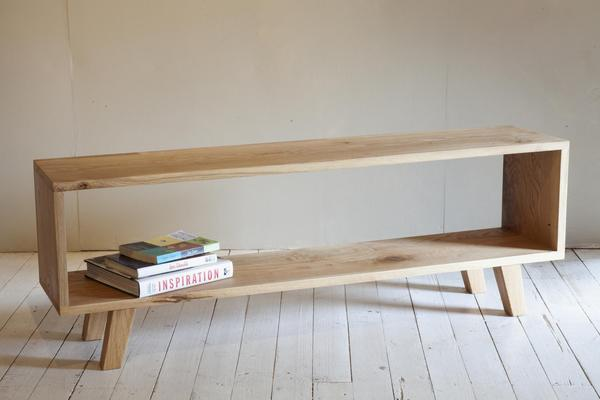 This is a cubed tv table, made from oak, with coffee table books on it.