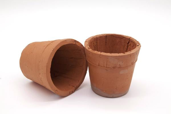 These are small terracotta pots. One is standing upright and the other on its side. These plant pots compliment any outdoor setting and are great for succulents.