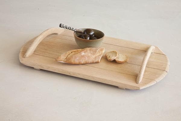 This is a wooden serving tray made from reclaimed oak barrels. It has wooden handles. This serving suggestion contains some olives and a baguette loaf.