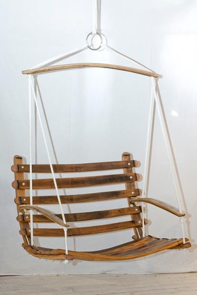 This is a wooden swing chair made from wine barrel staves. This hanging chair is suspended by white yachting rope.