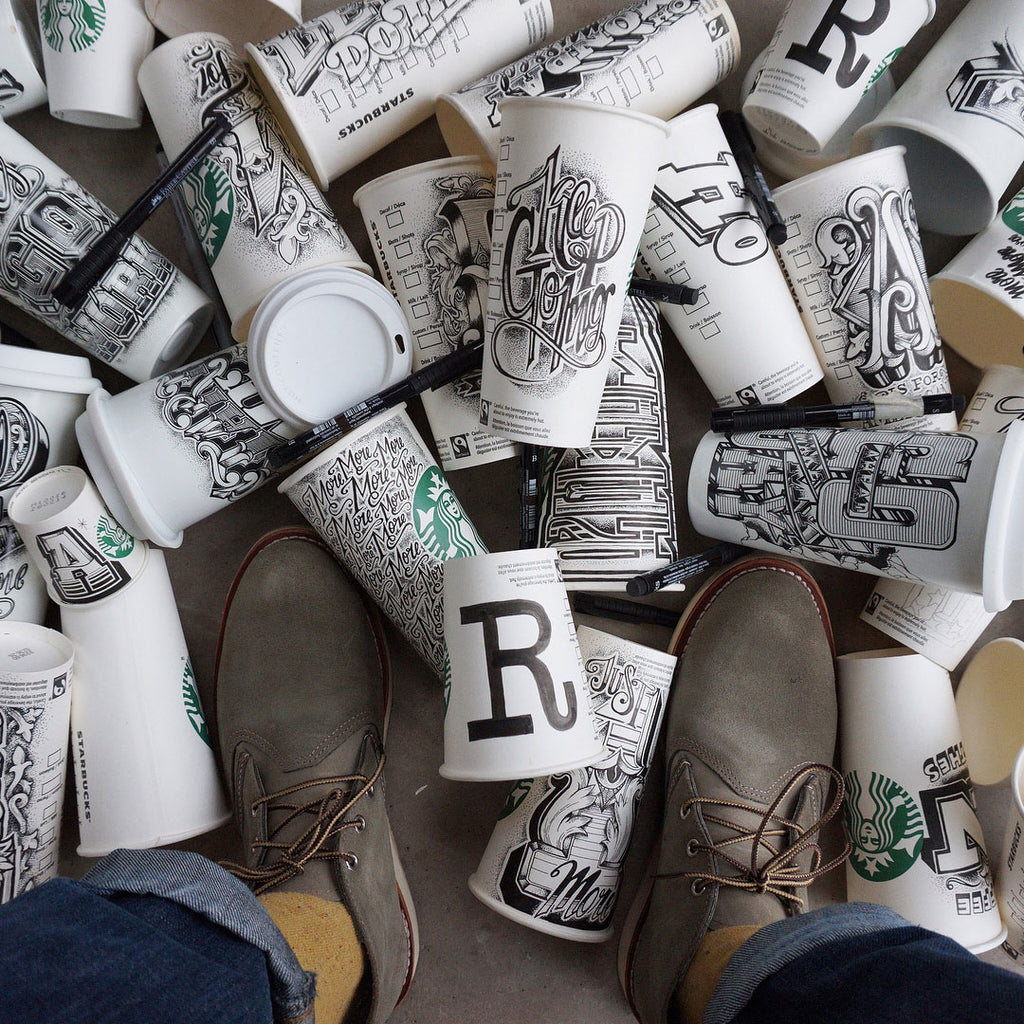 Coffee cups on the floor with each one illustrated by Rob Draper from @RobDraper1 on Instagram