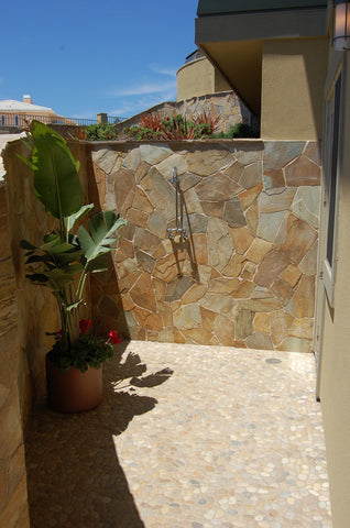 Outdoor shower floor in tan pebble tile