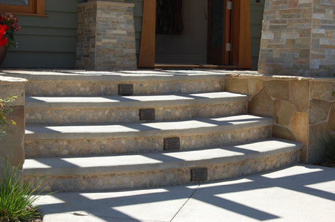 Outdoor entrance with tan pebble tile onthe risers