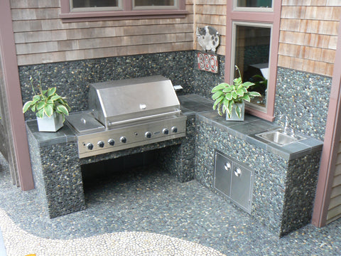 Outdoor barbeque are in river rock pebble tile and white pebble tile from Beyond Tile