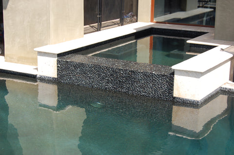 Pool fountain in blacks pebble tile and black standing pebble tile