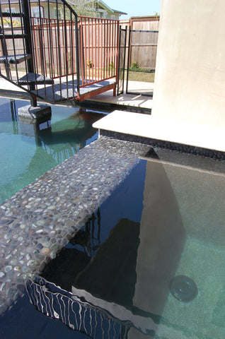 Pool coping and edge treatments in black pebble tile from Beyond Tile
