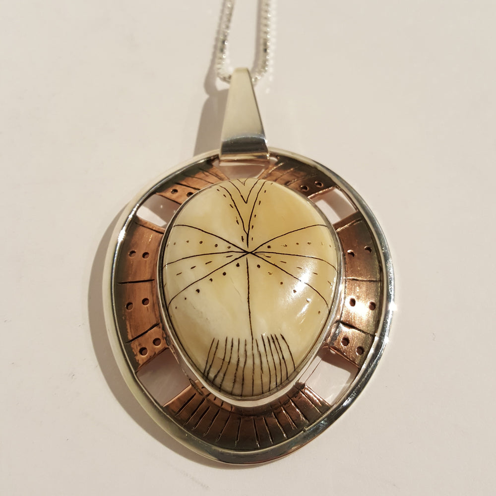 Tunit Pendant, with narwhal tusk ivory, copper, sterling silver and fine silver by Greg Morgan.