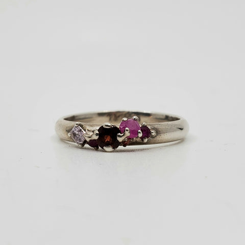 Pirate Treasure Ring in sterling silver with a crush of precious stones jostling for attention: ruby, purple and red sapphires, and garnet , 5 independently-set stones in all and one so tiny you wonder where the raspberry glow is coming from.  Size 7,75