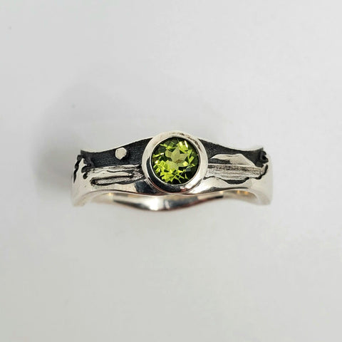 Peridot landscape at night ring in polished sterling silver against the oxidized matte black sky, size 7.5. The band is wavy with 7 mm for the tree and mountain tops and 5 mm for the water.