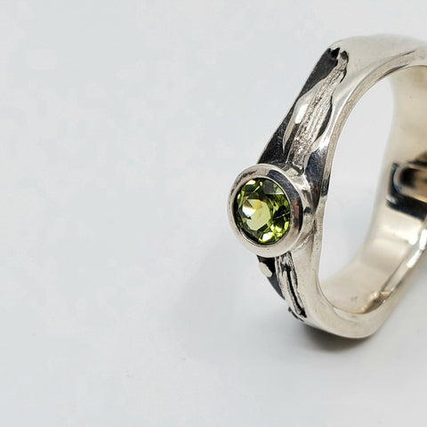 Peridot landscape at night ring in polished sterling silver against the oxidized matte black sky, size 7.5. The band is wavy with 7 mm for the tree and mountain tops and 5 mm for the water. side view