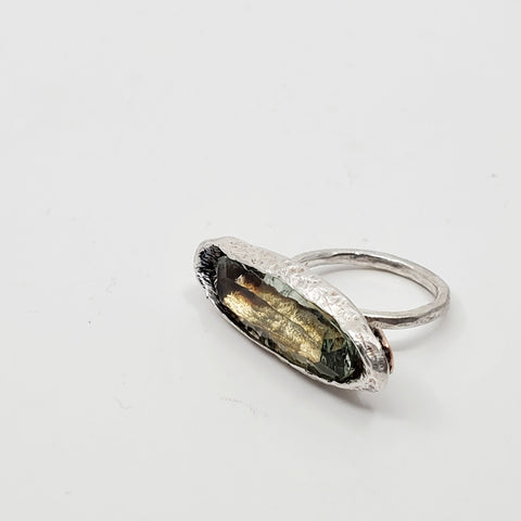 A sterling silver ring featuring an impressive oblong green quartz and recycled gold details. Size 6