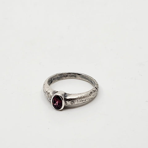 A hammered garnet set into the centre of two champagne diamonds with a sterling silver band. Size 6.25