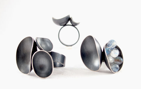 Wax and Wane Rings, of oxidized sterling silver, 3 x 2.5 x 1.5 cm high from the finger.  Three Bowls, in sizes 8 and 9, $360; Two bowls, one filled with faceted moonstone beads, 6.75, $410.