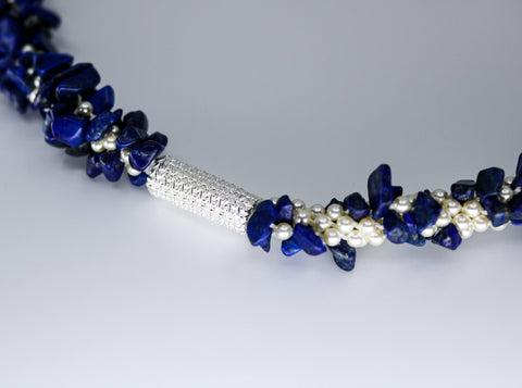 "Indigo Necklace. This lapis necklace braids in white Swarovski pearls through the kumihimo technique and has a hand-woven sterling silver clasp and elements.  Rotate its  19.5"" length to change the look. detail"