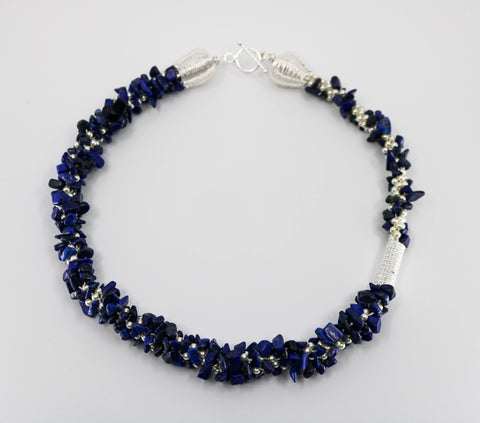"Indigo Necklace. This lapis necklace braids in white Swarovski pearls through the kumihimo technique and has a hand-woven sterling silver clasp and elements.  Rotate its  19.5"" length to change the look."